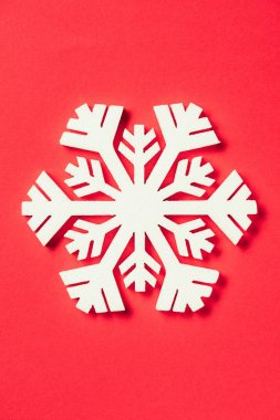 top view of paper snowflake on red background