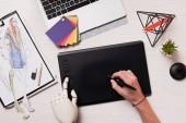 Fotografia mani femminili ritagliate alla scrivania design con mano del robot tramite penna e tavoletta grafica