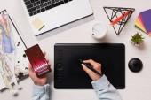 oříznutí zobrazení návrháře pomocí grafického tabletu, pera a smartphone s marketingem aplikace na obrazovce, ploché rozložení