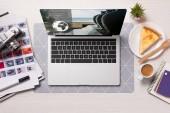 Fotografie kancelářský stůl s notebookem s rezervační stránky na obrazovce, ploché rozložení