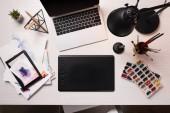 kancelářský stůl s notebookem, grafický tablet, pero a umělecké potřeby, ploché rozložení
