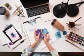 Gestutzter Designer arbeitet am Schreibtisch mit Laptop und Kunstgegenständen