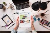 oříznutý pohled návrháře držení tabletu s ebay stránky na obrazovce na kancelářský stůl s výtvarné potřeby, ploché rozložení