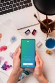 Ansicht des Designers am Schreibtisch hält Smartphone mit Twitter-app auf dem Bildschirm abgeschnitten, flach zu legen