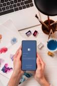 vágott tervezője íróasztal gazdaság smartphone-val facebook app képernyő kilátás, lapos feküdt