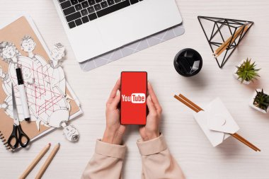 office desk with laptop and woman hands holding smartphone with youtube app on screen, flat lay