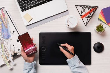 Cropped view of designer using graphics tablet, pen and smartphone with marketing app on screen, flat lay stock vector