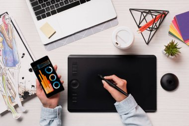 Cropped view of designer using graphics tablet, pen and smartphone with graphs on screen, flat lay stock vector