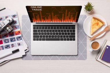 Office desk with laptop with online trading website on screen, flat lay stock vector