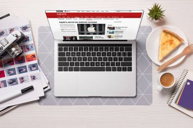 Office desk with laptop and bbc news website on screen, flat lay stock vector