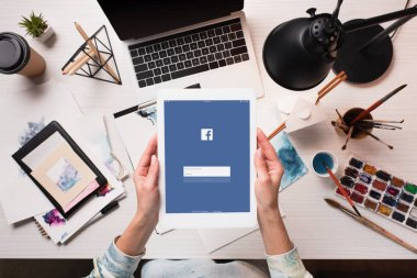 cropped view of designer holding tablet with facebook app on screen at office desk with art supplies, flat lay
