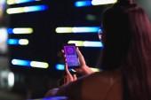 Fotografia vista posteriore di una ragazza che tiene smartphone con negozi apparecchio su strada con la luce al neon della sera, la città del futuro concetto