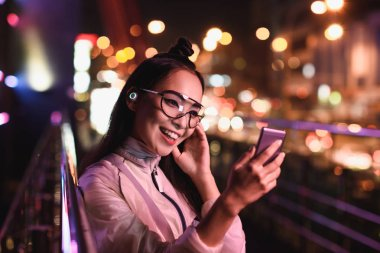 happy asian girl having video chat and using smartphone on street with neon light, city of future concept