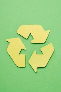 Top view of yellow recycle sign with arrows on green background