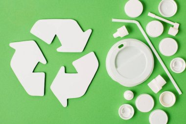 Top view of recycle sign and different kinds of disposable plastic garbage on green background