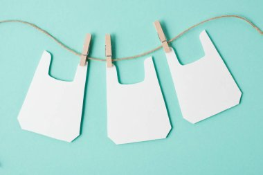 Models of packets hanging on rope on blue background