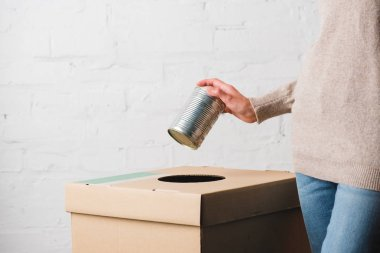 Partial view of woman throwing tin can in trash bin