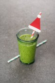 Fotografie Homemade green organic smoothie in glass with straws and christmas decoration