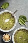 Fotografia Vista superiore di due ciotole con zuppa cremosa verde di spinaci e crostini