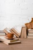 knihy, šálek kávy a suché podzimní list na dřevěný stůl