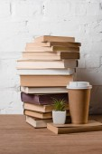 pile of books, green potted plant and coffee to go on wooden table