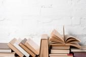 Fotografie knihy s deskami poblíž bílá cihlová zeď