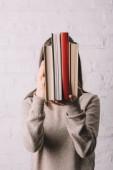 junge Frau versteckt Gesicht hinter Büchern nahe weißer Backsteinmauer