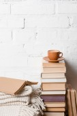 šálek kávy na hromadu knih poblíž bílá cihlová zeď
