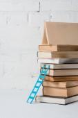 hromadu knih a malé modré krok žebřík poblíž bílá cihlová zeď