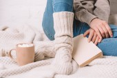 Fotografie cropped shot of girl in knitted socks sitting with book on warm blanket