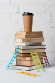 coffee to go on pile of books and small colorful step ladders