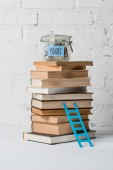 Photo pile of books, small step ladder and glass jar with savings and inscription books