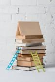 hromadu knih a malé žebříky bílé cihlové zdi