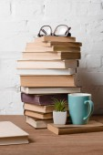 Fotografie pile of books, eyeglasses, potted plant and cup with hot beverage on wooden table