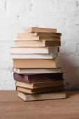 Detailní pohled na hromadu knih na dřevěný stůl