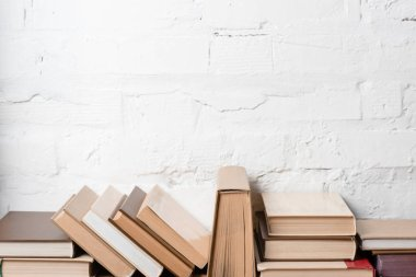 books with hardcovers near white brick wall, educational background