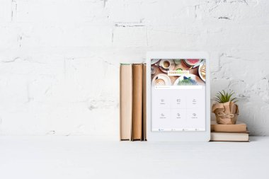 digital tablet with foursquare application, books and potted plant near white brick wall
