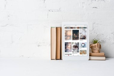digital tablet with pinterest application, books and potted plant near white brick wall