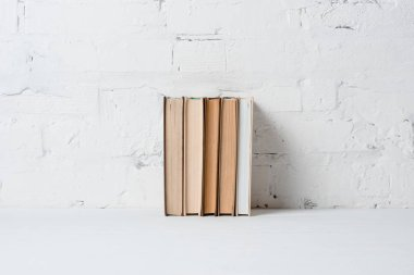 books near white brick wall, educational background