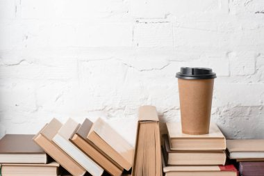Books with hardcovers and coffee to go near white brick wall stock vector