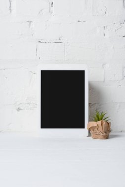 close-up view of digital tablet with blank screen and green potted plant near white brick wall