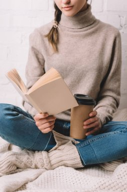 cropped shot of girl holding paper cup and reading book