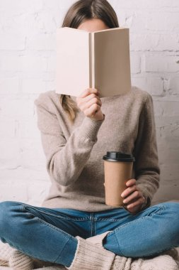 girl holding book and coffee to go in paper cup