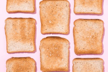top view of repetitive pattern of crispy toasts on pink surface