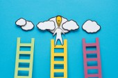 Photo cardboard man with light bulb head climbing one of three ladders on blue background, ideas concept