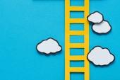 Draufsicht auf Papierleiter mit Wolken auf blauem Hintergrund, Zielsetzung Konzept