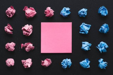 Top view of pink and blue crumpled paper balls with sticky note on black background, think different concept stock vector