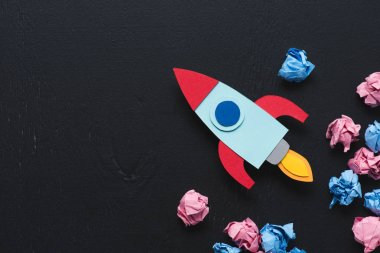 cardboard rocket with crumpled paper balls and copy space on black background, setting goals concept