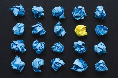 top view of blue crumpled paper balls with yellow one on black background, think different concept