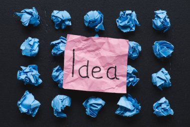 Top view of 'idea' word written on sticky note with blue crumpled paper balls on black background, ideas concept stock vector
